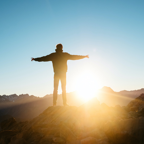 Someone feeling free on a mountain at sunset